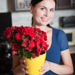 Young woman keeps a flower in a pot — Stockfoto