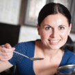 Young housewife cooks food in kitchen — Stock Photo #28493287