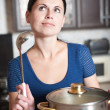 Young housewife cooks food in kitchen — Stock fotografie