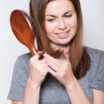 Young brunette beautiful woman combing long hairs — Stock Photo #38510835