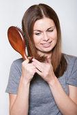 Young brunette beautiful woman combing long hairs — Stock Photo