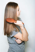 Young brunette beautiful lady combing long hairs — Stock Photo