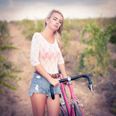 Vintage beautiful fashion girl with bicycle — Stock Photo