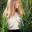 Stock Photo: Young beautiful woman poses in green thickets