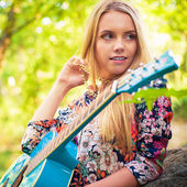 Vintage looking photo of a beautiful girl with a guitar — Stock Photo