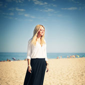 Young beautiful woman blonde poses on a beach — Stock Photo