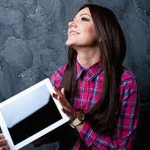 Den unga flickan drömmar och innehar pekplattan — Stockfoto