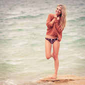 Happy young girl poses on a beach — Stock fotografie