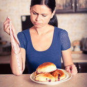 Young woman holds pie and a measuring tape — Stock Photo