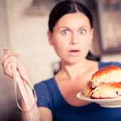 Young woman holds pie and a measuring tape — Stock fotografie