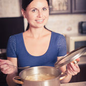 Young housewife cooks food in kitchen — Stock Photo