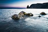 Vallende stenen in de zee in de zonsondergang — Stockfoto