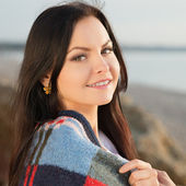 Brunette woman outdoors in check pattern plaid — Stock Photo