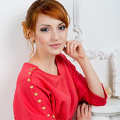 Young fashionable woman posing in red dress — Stock Photo