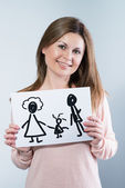 Woman holding picture with happy family — Stock Photo
