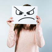 Woman holding a cardboard with a angry face — Stock Photo