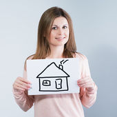 Woman holding picture with house — Stock Photo