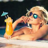 Girl with fresh orange juice in luxury pool — Stock Photo
