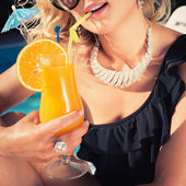 Beautiful, suntanned, young woman drinks cocktail — Stock Photo