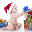 Baby in a cap of Santa Claus with gifts — Stock Photo
