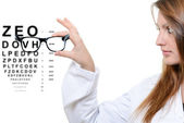 Optician giving a patient glasses to try on — Stock Photo