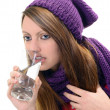 Close-up of sick pretty girl drinking water from glass — Stock Photo