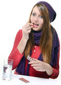Cute girl taking drug against a white background — Stock Photo