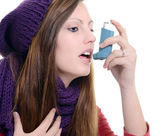 Woman with asthma using an asthma inhaler — Stock Photo