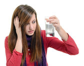 Woman taking pills holding a glass of water in office — Stock Photo