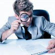 Handsome businessman with magnifying glass study contract — Stock Photo #20101329