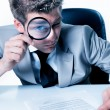 Stock Photo: Handsome businessmwith magnifying glass study contract