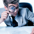 Foto de Stock  : Handsome businessmwith magnifying glass study contract