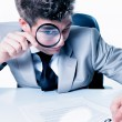 Businessman with magnifying glass reading the fineprint in a con - Stock Photo