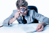 Handsome businessman with magnifying glass study contract — Stockfoto