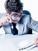 Businessman with magnifying glass reading the fineprint in a con — Stock Photo