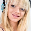 Blond Teenage girl listening to music with blue headphone — Stock Photo