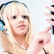 Stock Photo: Attractive blond girl listening to music on her smartphone