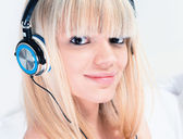 Pretty blond girl listening to music on her smartphone — Foto de Stock