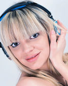 Attractive girl listening to music with blue headphone — Stockfoto
