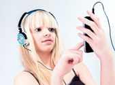 Attractive blond girl listening to music on her smartphone — Stock Photo