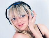 魅力的な女の子の青のヘッドフォンで音楽を聴く — ストック写真