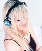 Cute blond girl listening to music on her smartphone — Stock Photo