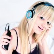 Stock Photo: Pretty blond girl listening to music on smartphone