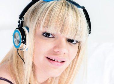 Attarctive blond girl listening to music on headphone
