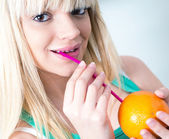 Girl drinking an orange from a straw — Stock Photo