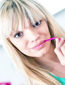 Handsome girl drinking an orange from a straw — Stock Photo