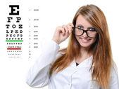 Beautiful smiling female doctor holding eyeglasses — Stock Photo
