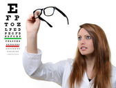 Pretty doctor portrait with glasses in her hand — Stock Photo