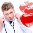 Stock Photo: Cheerful male doctor listening heartbeat