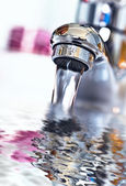 Water tap with flowing water in the bathroom — Stock Photo